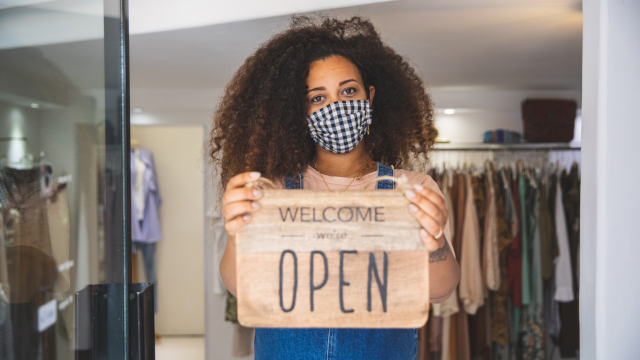 "Photo of an African American woman entrepreneur wearing a face mask and holding a sign that reads ""Welcome, we are open"""